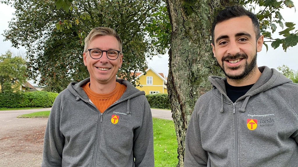 Två män står utomhus och ler mot kameran.