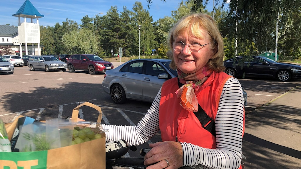 Äldre kvinna med cykel och matkasse i solskenet på en parkeringsplats.