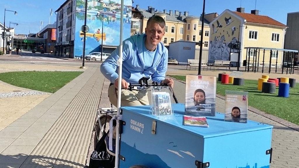 """En person sitter på en cykelvagn med texten """"Oskarshamn."""""""
