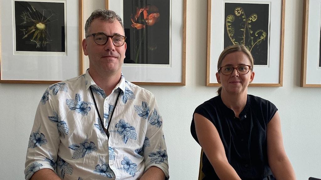 En man och en kvinna tittar in i kameran. På väggen bakom hänger fyra tavlor med blommiga motiv.