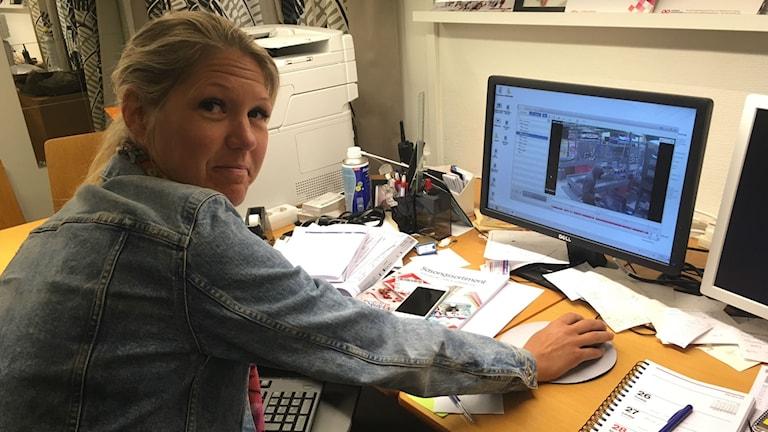 Therese Nilsson framför dataskärm med övervakningsbild av rånförsöket.
