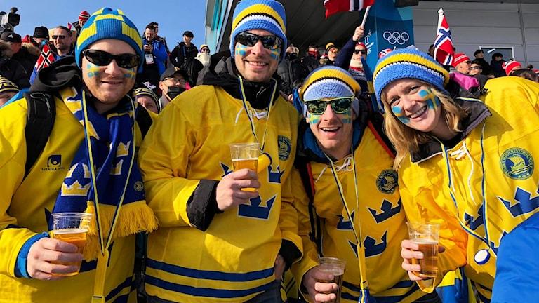Henrik Aronsson, Albin Martinsson, Anders Franklund och Lisa Hammarlund med blågula tröjor och mössor.