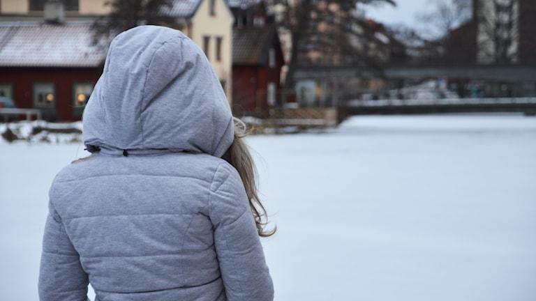 En ensam tjej tittar ut över fruset vatten.