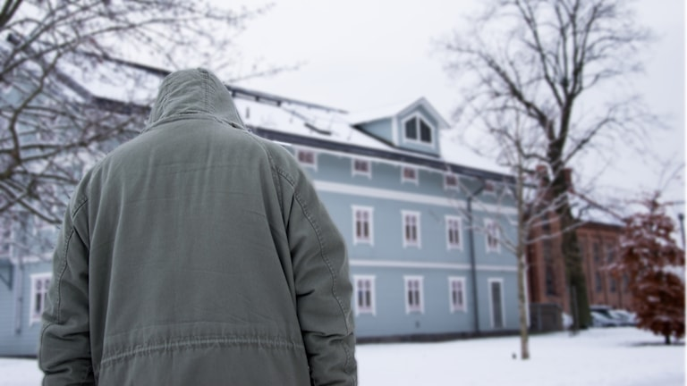 Man i luva framför Eskilstuna Stadsmission, snö ute.