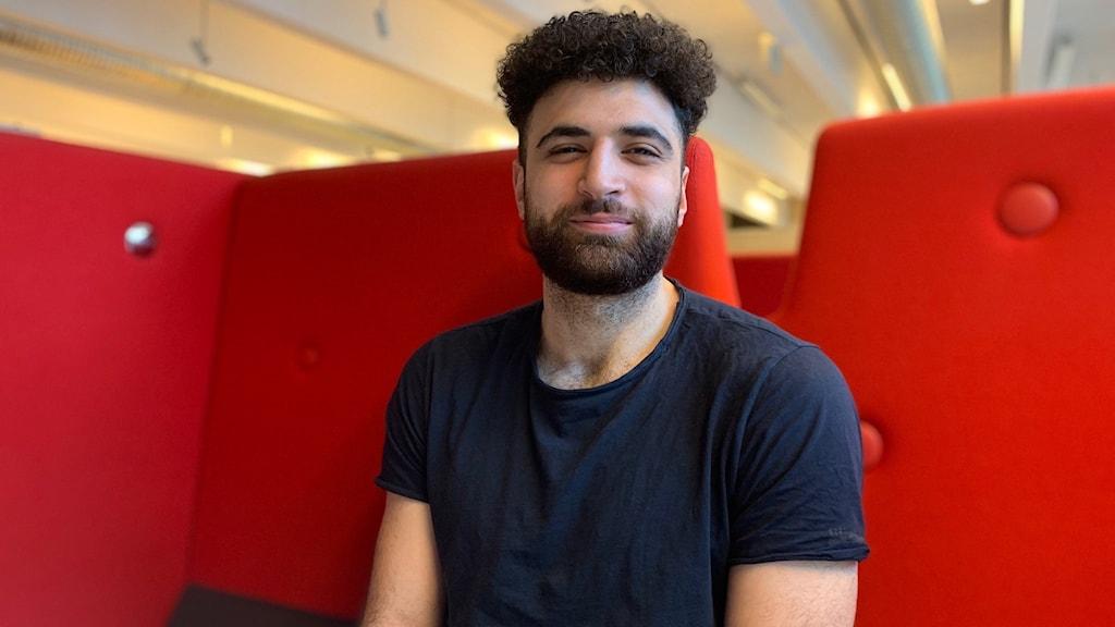 Yngre man med skägg sitter i röd soffa och ler.