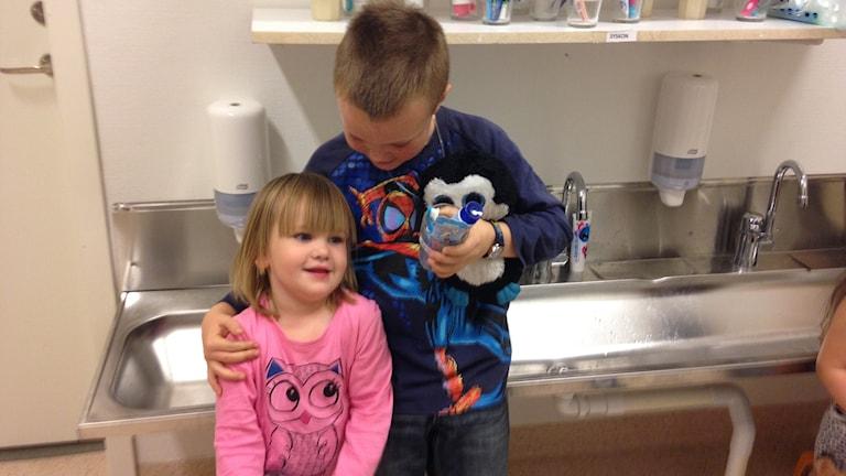 Två barn som är syskon står nära varandra.