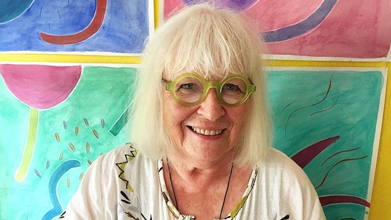 Gudrun Sjödén sitter framför en färgglad vägg. Ler.
