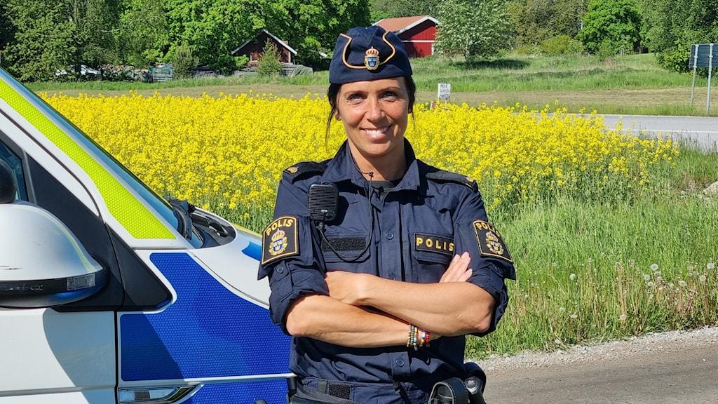 Anna-Karin Wahlgren vid polisbil med ett gult rapsfält i bakgrunden.