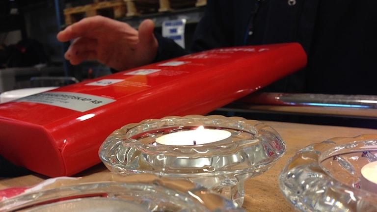 Brandfilt i förpackning och levande ljus. Foto: Linnéa Wannefors/Sveriges Radio.