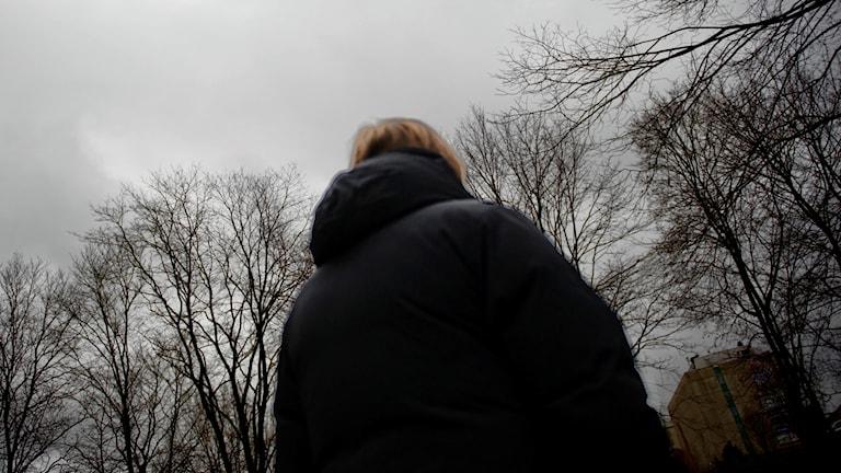 Kvinna tittar upp mot svarta träd