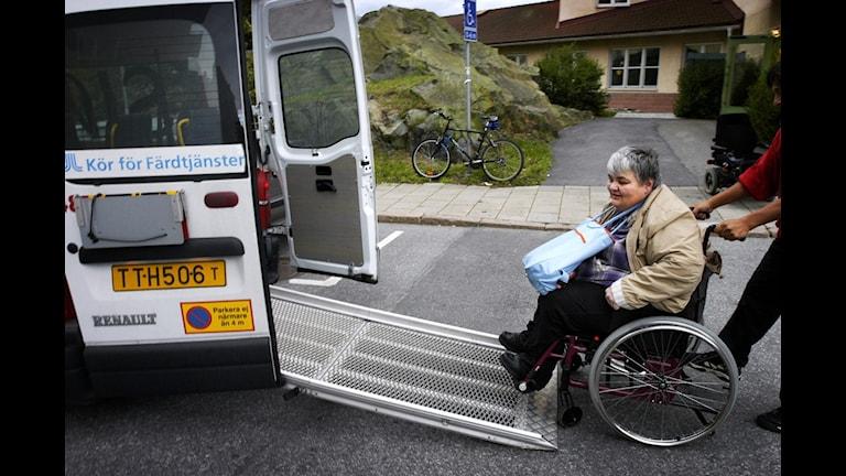 Kvinna i rullstol intill en färdtjänstbil. Foto: Malin Hoelstad/TT.