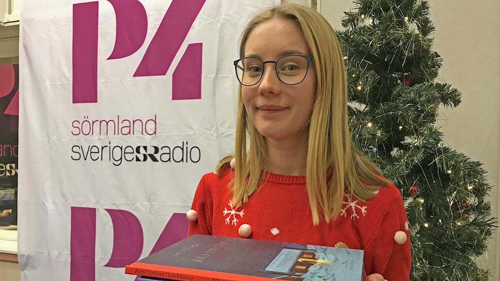 Agnes Lindholm håller i tre böcker.