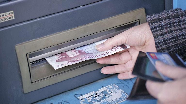 En hand tar tag i en femhundralapp som matas ut från en bankomat. Foto: Fredrik Sandberg/Scanpix.