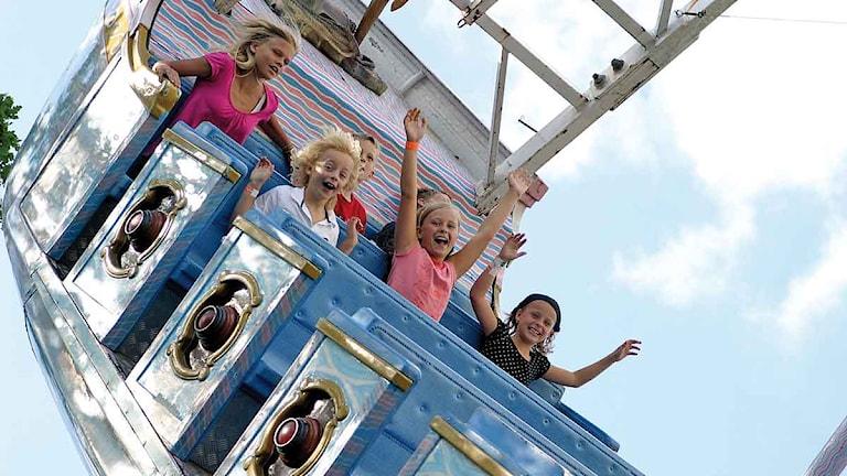 Barn och ungdomar sitter i en karusell med uppsträckta armar. Foto: Parken Zoo.
