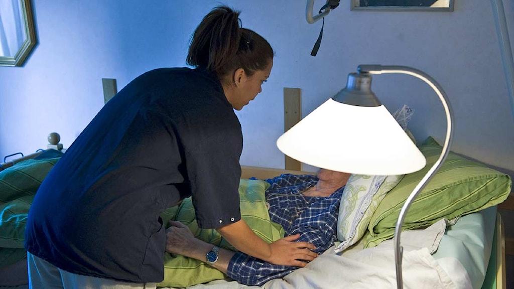 En kvinna i blå rock lutar sig över en säng med en äldre person. Foto: Henrik Montgomery/Scanpix.