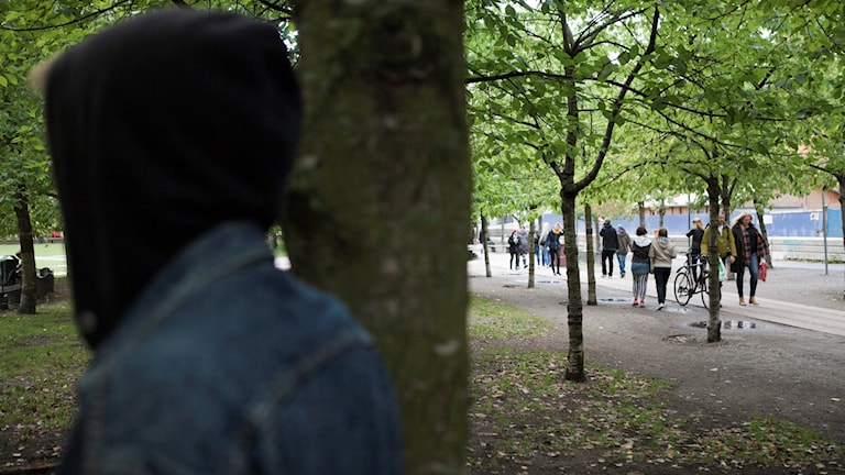 Anonym person i huva i en park.