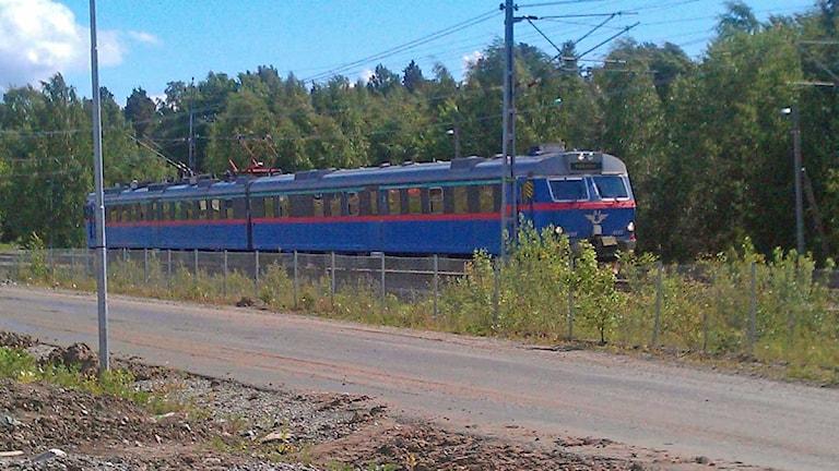 Blått tåg rusar fram vid en grusväg. Foto: Fredrik Blomberg/Sveriges Radio.