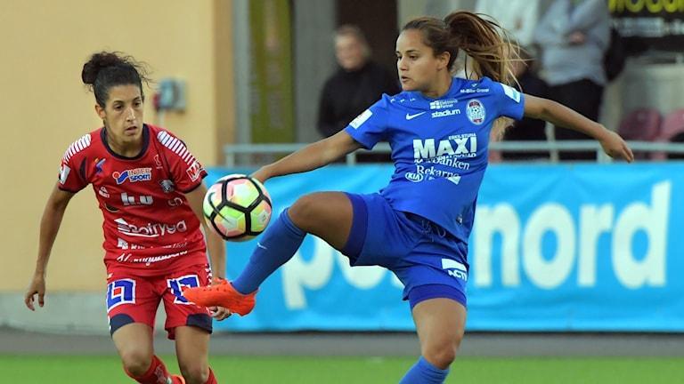 Kvinnlig fotbollsspelare tar emot en boll i luften.