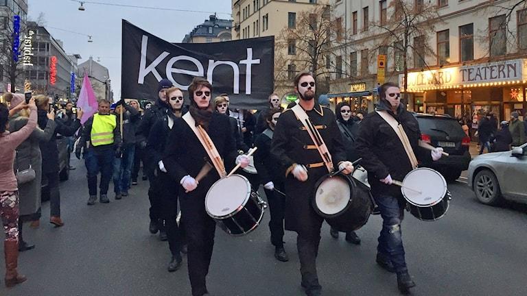 Folk i parad med trummor och stor Kent-flagga.