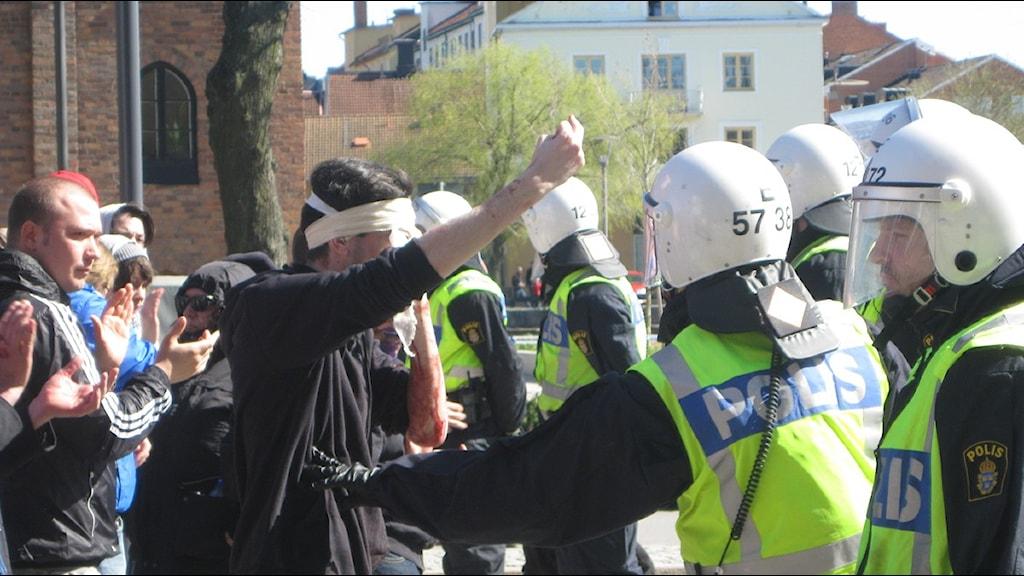 En skadad man och motdemonstranter i Eskilstuna. Foto: Fredrik Blomberg/Sveriges Radio.