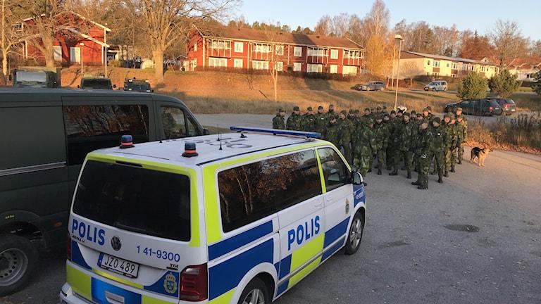 En polisbuss och soldater ur hemvärnet står på en parkering.