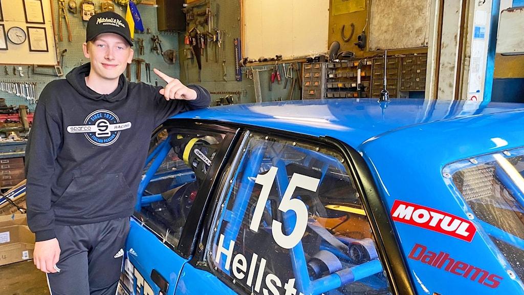 En kille står i ett garage med en blå rallycrossbil.