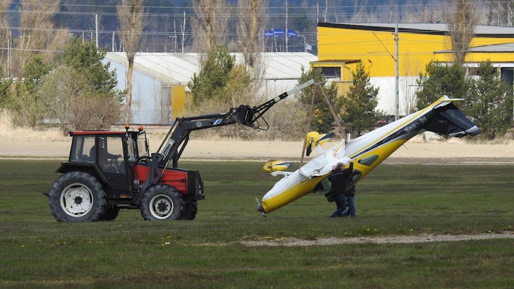 Litet flygplan lyfts bort med traktor.