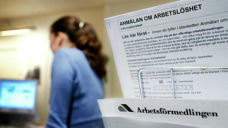 """En blankett med texten """"Anmälan om arbetslöshet"""", i bakgrunden en kvinna framför en datorskärm. Foto: Henrik Montgomery/Scanpix."""
