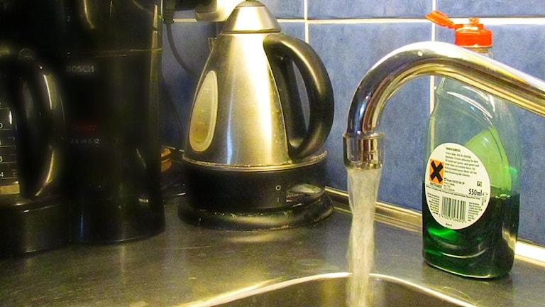 Vatten rinner ur en diskbänkskran.