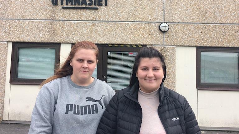 Två elever framför Duveholmsgymnasiet
