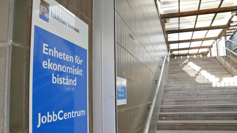 """En blåvit skylt med texten """"Enheten för ekonomiskt bistånd"""", i bakgrunden en trappa. Foto: Petra Levinson/Sveriges Radio."""