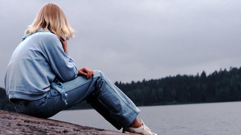 En kvinna sitter på en klippa.