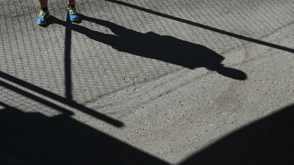 Ett par fötter i gympaskor, skuggan av en person och ett staket på asfalt. Foto: Fredrik Sandberg/Scanpix.