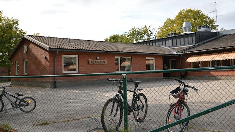 Skolbyggnad i tegel och en tom asfaltsplan, i förgrunden ett staket och ett par cyklar. Foto: Andreas Jennersjö/Sveriges Radio.