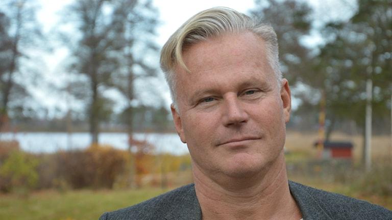 Hans Ekström utomhus, i bakgrunden tallar och en vattenspegel. Foto: Petra Levinson/Sveriges Radio.