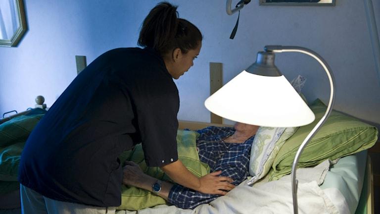 En sköterska i blå rock böjer sig över en äldre kvinna i en säng. Foto: Henrik Montgomery/TT.