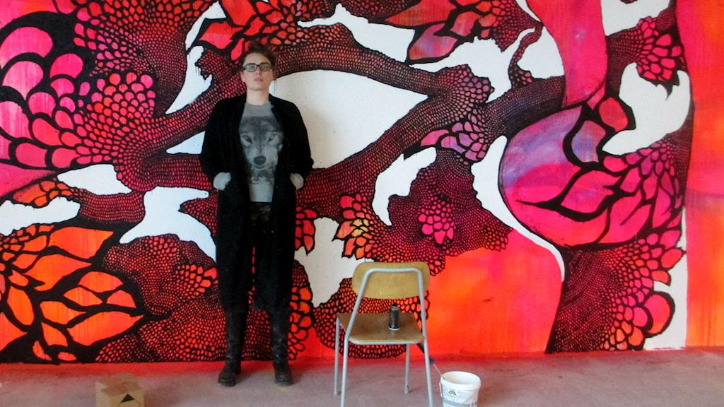 Konstnär står framför en färgglad vägg i ceris, lila och svart.Foto: Johanna Jennische/Sveriges Radio