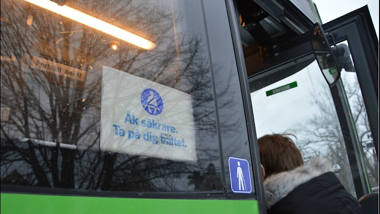 """En passagerare kliver på en buss, i förgrunden en skylt med texten """"Åk säkrare. Ta på dig bältet."""" Foto: Petra Levinson/Sveriges Radio."""