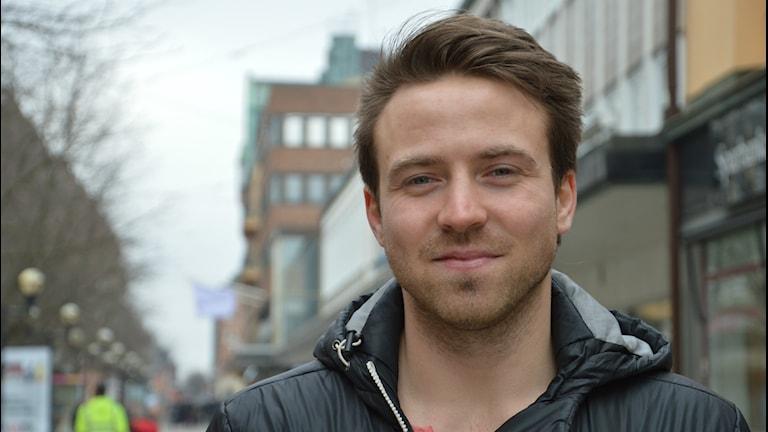 En leende Robin Andersson, i bakgrunden hus och gågata. Foto: Petra Levinson/Sveriges Radio.