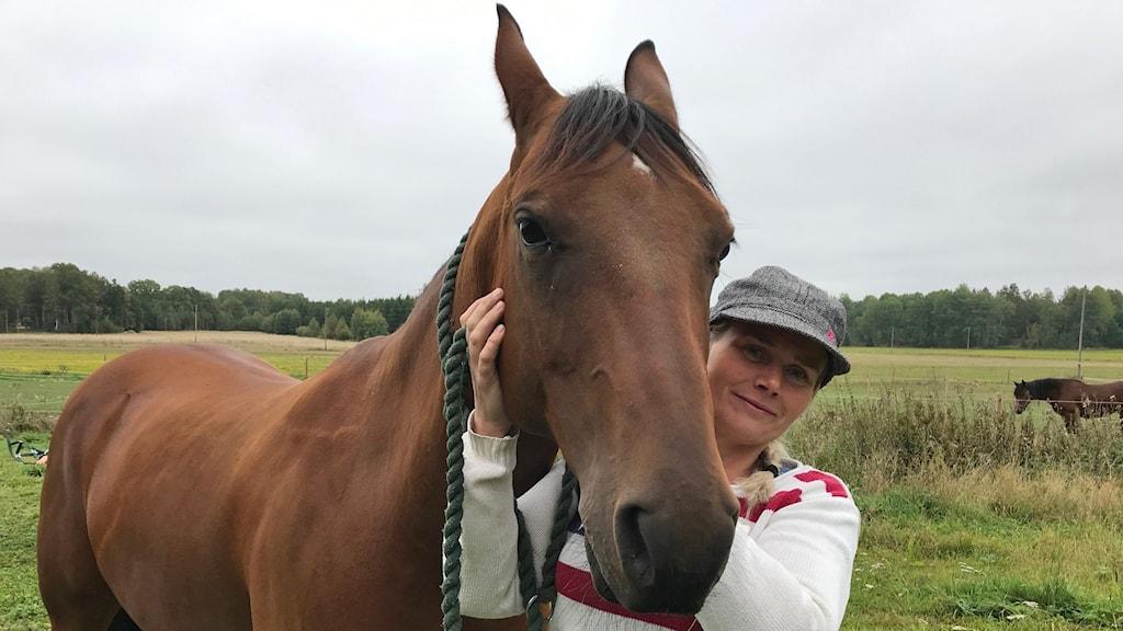 Lotta Wisén från Ärla står bredvid en häst.