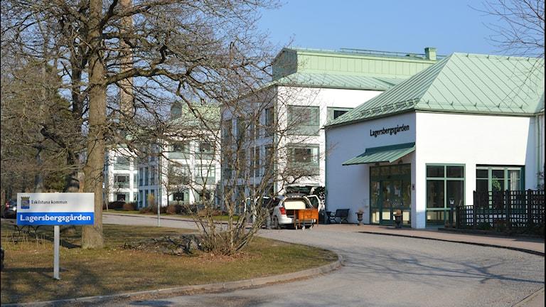 """Vita hus med gröna tak, i förgrunden en skylt med texten """"Lagersbergsgården"""". Foto: Petra Levinson/Sveriges Radio."""
