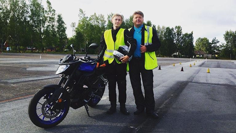 Två män står framför en motorcykel på en motorbana.