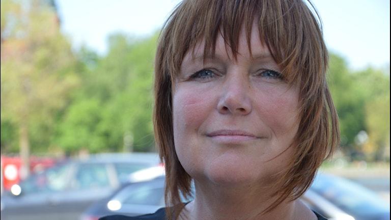 Sarita Hotti, i bakgrunden bilar och gröna träd. Foto: Petra Levinson/Sveriges Radio.