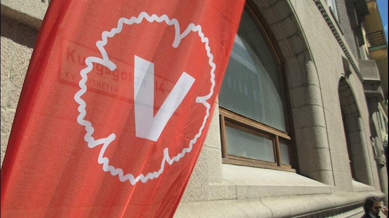 En röd flagga med Vänsterpartiets logga vajar framför en husfasad. Foto: Lina Lundgren/Sveriges Radio.