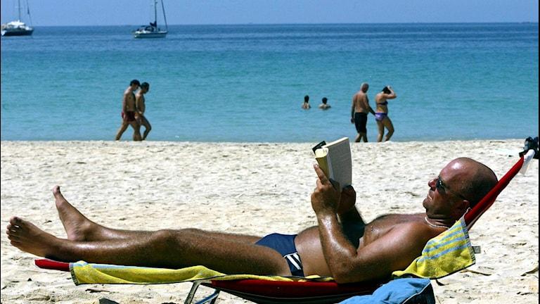 En västerländsk, solbränd man läser en bok på en vit strand, i bakgrund turkost vatten. Foto: Teh Eng Koon/TT.