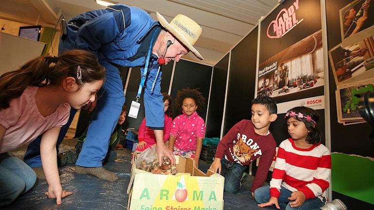Lennart Larsson ställer ned en låda lökar hos några barn från Årbygatans förskola. Foto: Jacob Hansson/Sveriges Radio