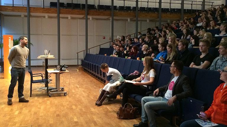 Elever och en föreläsare i aulan. Foto: Fredrik Lorenzoni/Sveriges Radio.