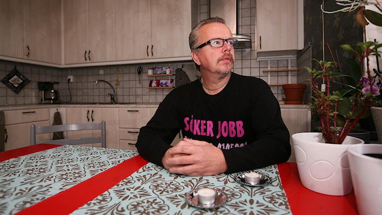 Sören sitter vid sitt köksbord och titttar ut genom fönstret. Foto: Jacob Hansson/Sveriges Radio