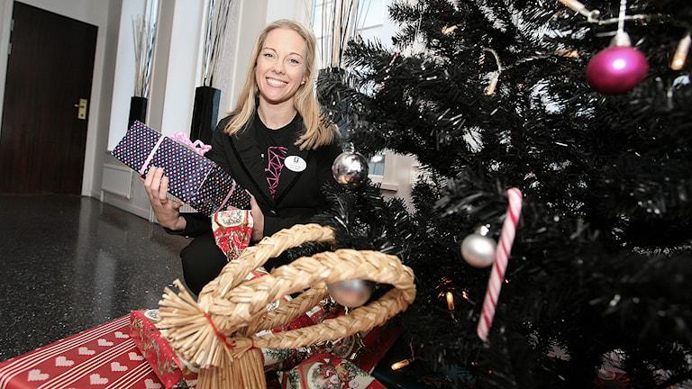 Catrin Jennsjö sitter intill julgranen med paket i handen. Foto: Jacob Hansson/Sveriges Radio