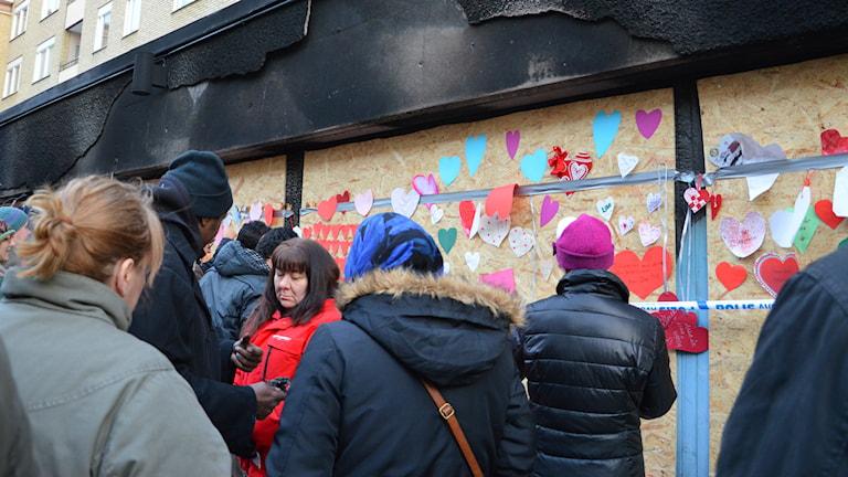 Människor fäster pappershjärtan på vägg. Foto: Ida Lindhagen/Sveriges Radio
